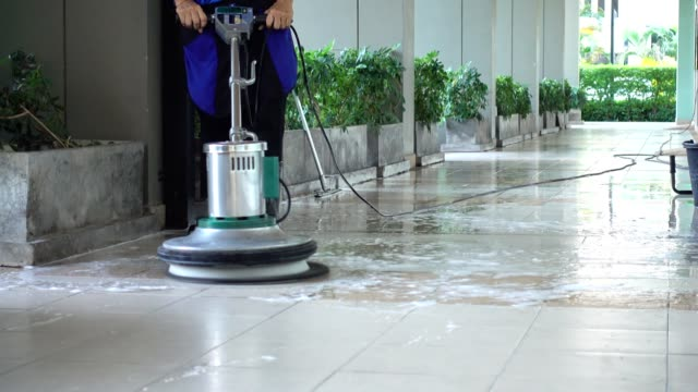 cleaning service team cleaning floor with scrubber machine and cleaning in process label - cleaning stock videos & royalty-free footage