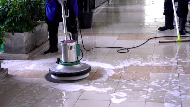 cleaning service team cleaning floor with scrubber machine and cleaning in process label - cleaning agent stock videos & royalty-free footage