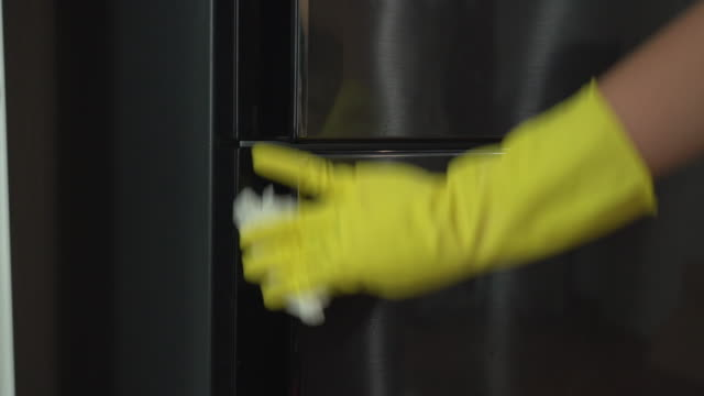 cleaning surface of refrigerator door by ethanol spray and disposable paper to protect life from covid-19 - rubbing stock videos & royalty-free footage