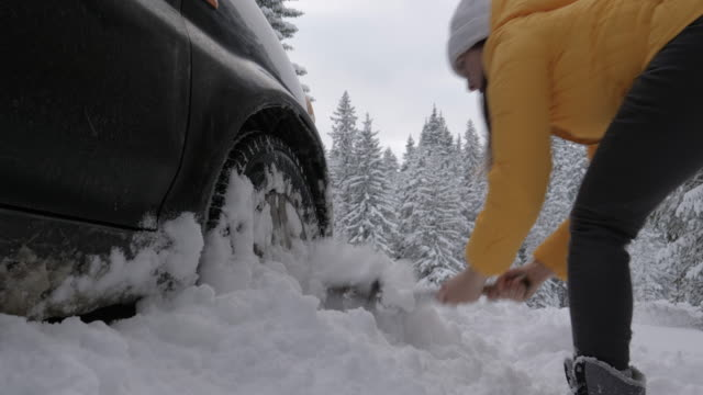 cleaning the car and sweeping after the first snow. emergency lights. car issues in the middle of nowhere in bad weather. car insurance. one woman on the road. - snowplough stock videos & royalty-free footage