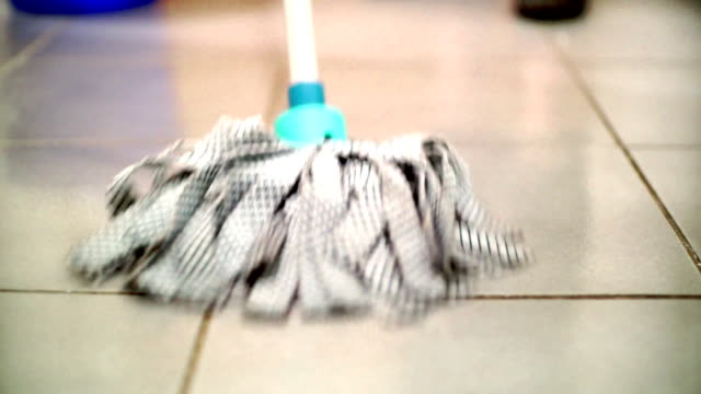 Cleaning the floor with a mop.