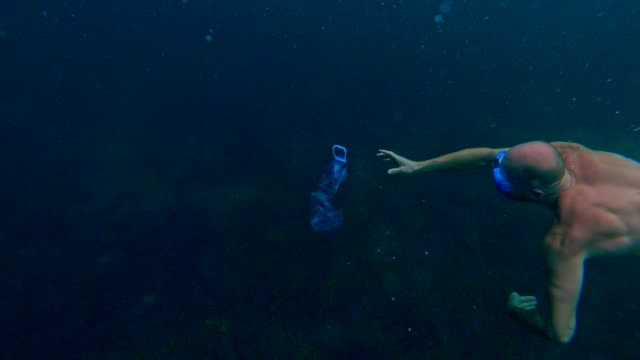 Cleaning the ocean. Man catching pet bottle under sea surface