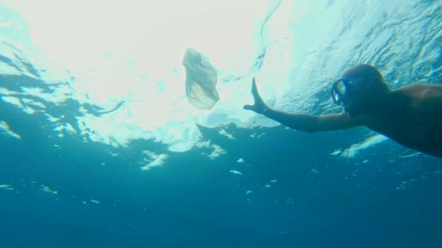 Cleaning the ocean. Man catching plastic bag under sea surface