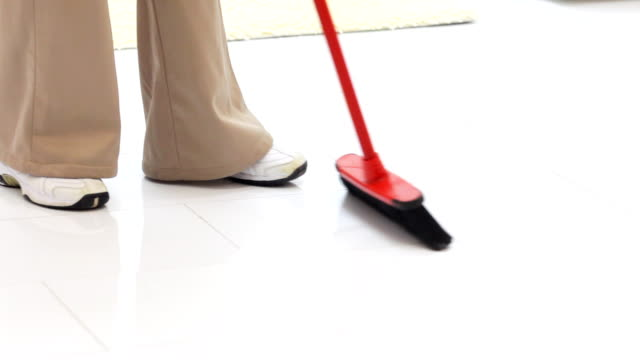 Cleaning woman sweeping floors with broom.