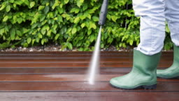 cleaning wooden terrace with high pressure washer by gardener in wellingtons