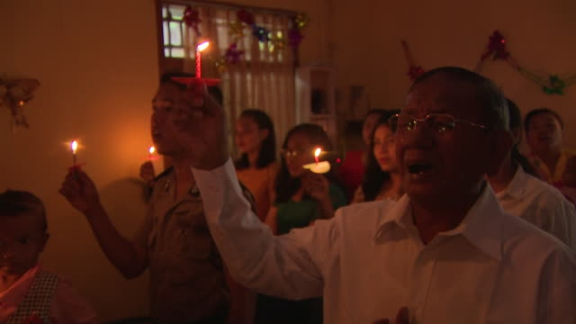 interior shots of christians singing and holding candles during a mass at church on december 25, 2018 in carita, banten province, indonesia. - ミサ点の映像素材/bロール