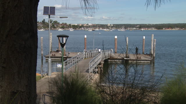 clear blue skies, a wooden jetty leads down to the georges river / cruise boats moored at a jetty / captain cook bridge, across the georges river... - floating moored platform stock videos & royalty-free footage