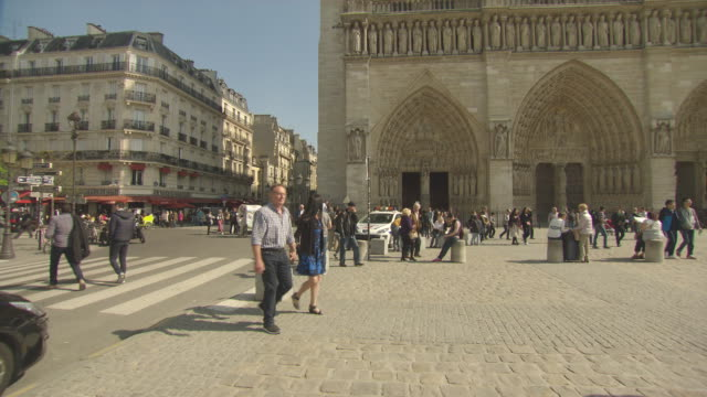 clear blue skies square and pedestrians tourists in front of cathedral camera pans up towards notre dame / close up of statues around the top of... - notre dame de paris stock videos & royalty-free footage
