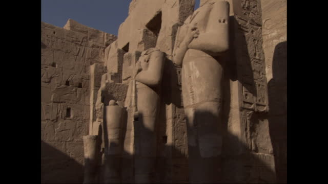 a clear blue sky contrasts sharply with the ruins of tall headless egyptian statues and adobe walls covered in hieroglyphs. - decapitated stock videos & royalty-free footage