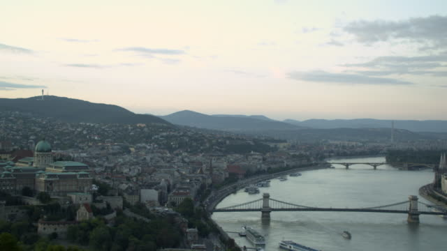 Clear Day-long establishing shot over Danube featuring the Chain Bridge in Budapest, Hungary. From one side of the city to the other then zooms out featuring both sides of the river. Travel destination
