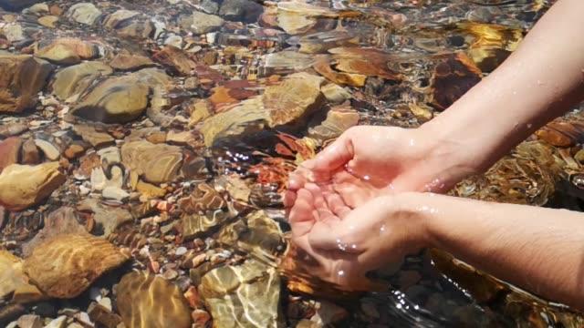 スローモーションで手を女性の透明な自然水 - 湧水点の映像素材/bロール