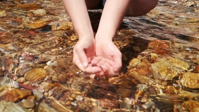vídeos de stock, filmes e b-roll de água clara natural na mulher mãos em câmera lenta - fonte