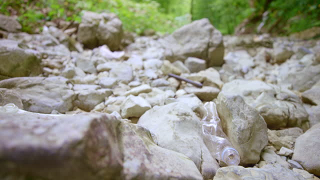clear plastic bottle lying in a dry riverbed - rock stock videos & royalty-free footage