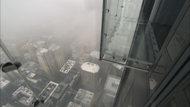 a clear platform reveals a view of foggy chicago. - sears tower stock-videos und b-roll-filmmaterial