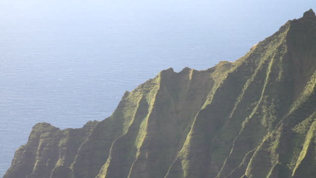 clear skies above calm ocean around kauai island - butte rocky outcrop stock videos & royalty-free footage