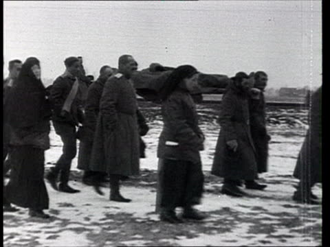 1915 montage b/w clergyman leading mourners carrying bodies of two russian soldiers towards cemetery/ russia - prima guerra mondiale video stock e b–roll