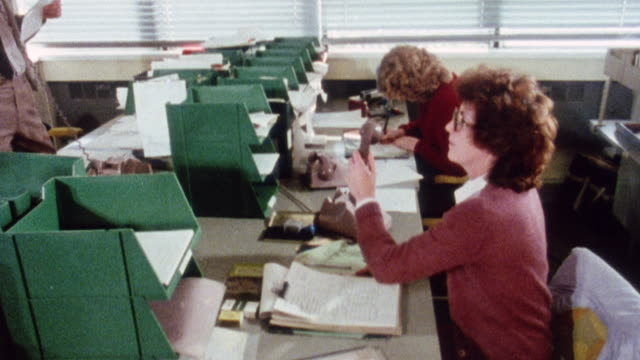 stockvideo's en b-roll-footage met montage clerical worker answering a call at the vat center and using a computer to find information / london, england, united kingdom - 1983