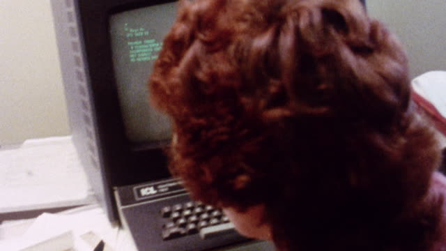 MONTAGE Clerical worker using a computer to look up information in the VDU system for a caller / London, England, United Kingdom