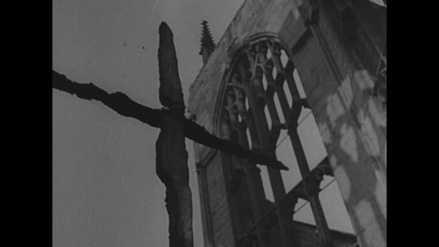 clerics walk on center aisle of the ruined st. michael's cathedral / tilt up of charred cross and window with the sky beyond / bishop neville vincent... - コベントリー点の映像素材/bロール