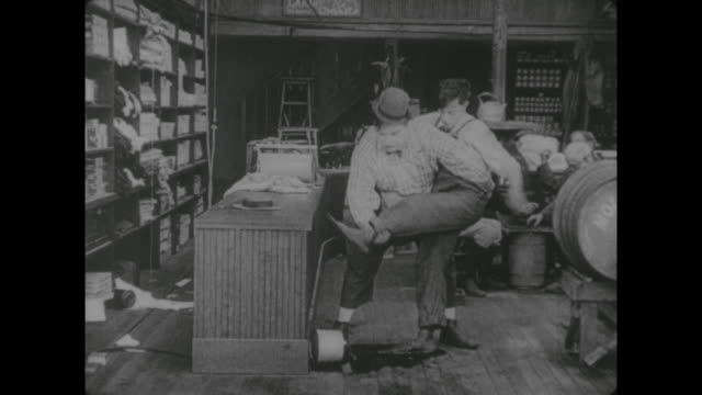 stockvideo's en b-roll-footage met 1917 clerk (fatty arbuckle) attempts to free customer (buster keaton) from syrup laden floor - kleverig