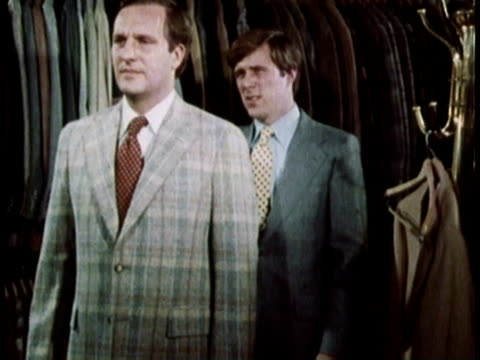 stockvideo's en b-roll-footage met 1979 ms clerk attending to customer trying on suit in men's clothing store / united states - herenkleding