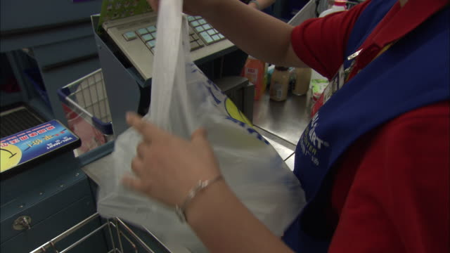 vídeos de stock e filmes b-roll de ms clerk giving empty plastic bag to customers in supermarket, customers packing shopping, beijing, beijing, china - saco de plástico