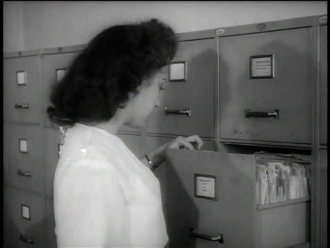 1946 ms clerk pulling a file out of a filing cabinet and examining its contents / united states - filing cabinet stock videos & royalty-free footage
