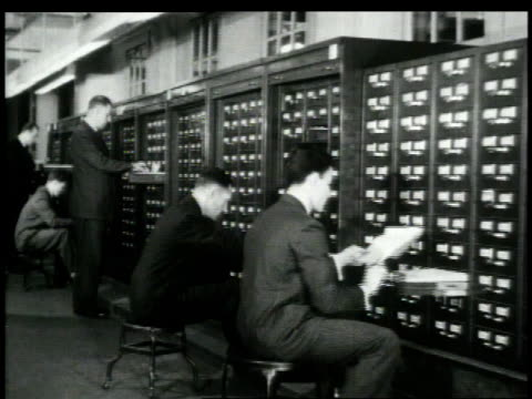 1948 MONTAGE clerk searching through card catalog / New York City, New York, United States