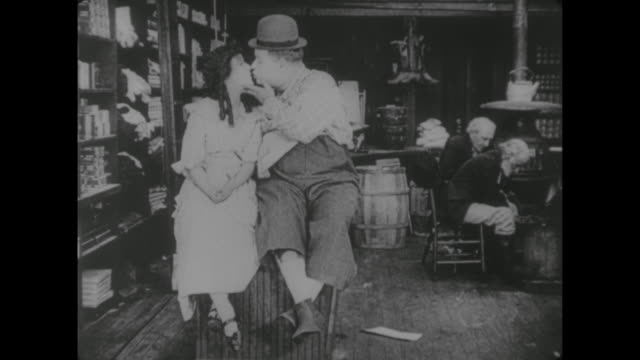 1917 clerk (fatty arbuckle)sits, flirts, chatters and kisses fellow clerk (alice lake) as they sit on store counter - fatty arbuckle stock videos and b-roll footage