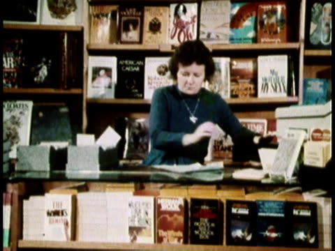 vídeos de stock, filmes e b-roll de 1979 montage clerk working in bookstore / united states - livraria