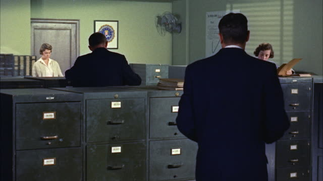 vidéos et rushes de ms tu td clerks checking files in small office / washington d.c. , united states - 1950 1959