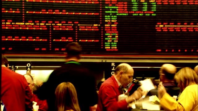 Clerks in yellow jackets work with brokers in red jackets on the floor of the Chicago Mercantile Exchange. Available in HD.