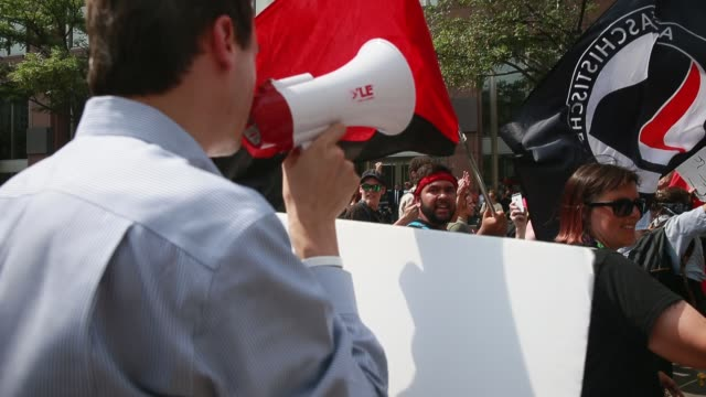 a counter protester saying that socialism sucks follows members of the industrial workers of the world begin to march on the final day of the 2016... - socialism stock videos & royalty-free footage