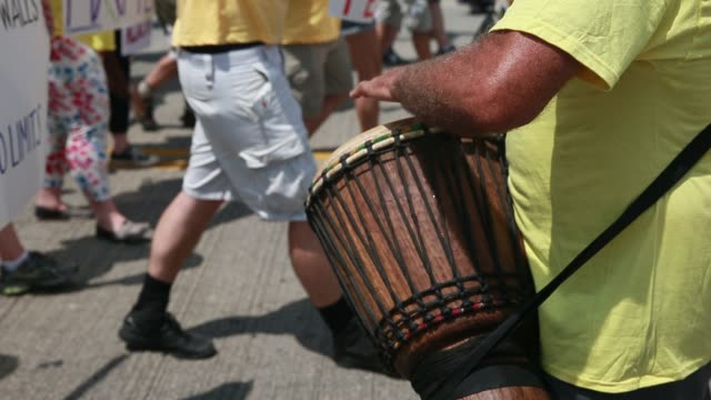 a man beats on a drum as protesters participate in the stand against trump march over the hope memorial bridge on the final day of the 2016... - republikanischer parteitag stock-videos und b-roll-filmmaterial