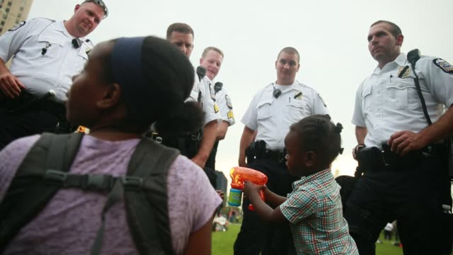cleveland, ohio, usa: avery jordan sprays bubbles with a toy gun as police officers watch in amusement on the final day of the 2016 republican... - toy gun stock videos & royalty-free footage