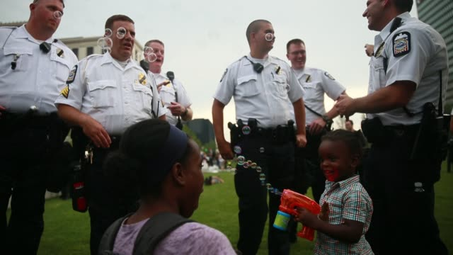 avery jordan sprays bubbles with a toy gun as police officers watch in amusement on the final day of the 2016 republican national convention in... - toy gun stock videos & royalty-free footage