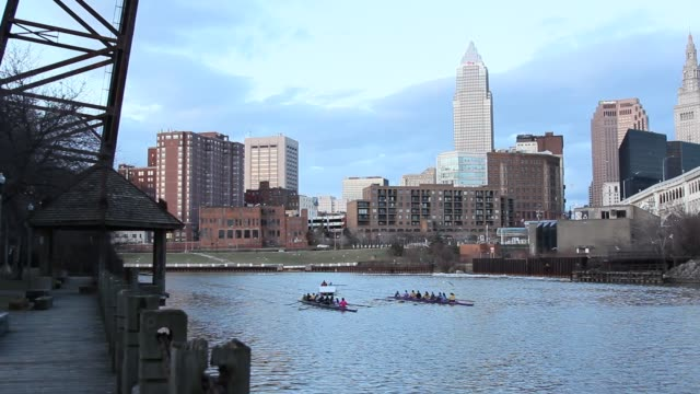 cleveland rowing club practicing on cuyahoga river with cleveland skyline view on the background in the clear spring evening - fiume cuyahoga video stock e b–roll