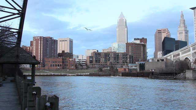 cleveland skyline view with veterans memorial bridge in the clear spring evening - fiume cuyahoga video stock e b–roll