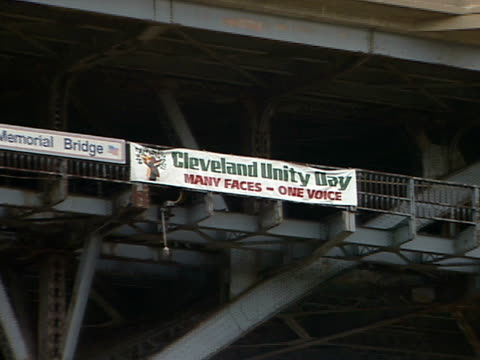 cleveland unity day banner attached to detroit superior bridge zoi ws bridge over cuyahoga river w/ red center street swing span bridge bg cuyahoga... - fiume cuyahoga video stock e b–roll