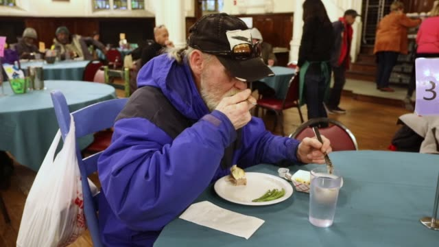 client eats a meal at the broad street ministry which serves thousands of free meals five days per week while also providing the homeless with a mail... - united states postal service stock videos & royalty-free footage