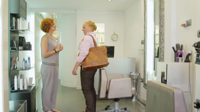 WS client (mature woman) entering hairdressing salon, being welcomed by female hairdresser and shown to chair; the two discuss the clients wishes