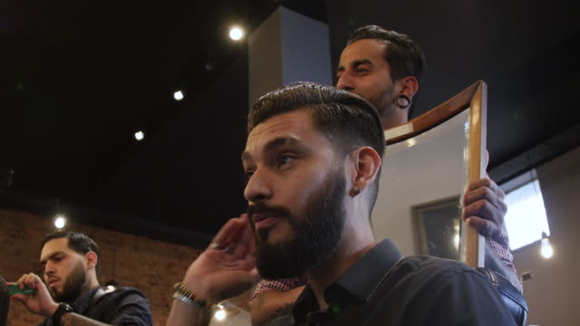 client examining haircut in mirror held by barber - cutting hair stock videos and b-roll footage