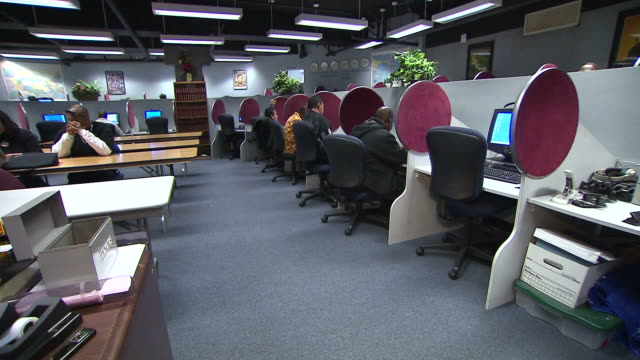 PAN Clients working at computer workstations and at tables in a Mission workroom with files on a desk covering Boost and GED programs / Los Angeles...