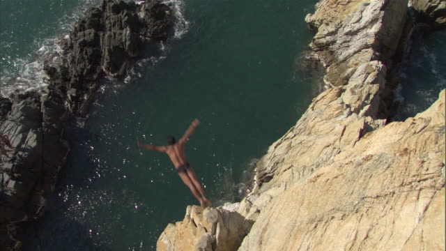 vidéos et rushes de ws ha cliff diver leaping off cliff into ocean / acapulco, guerrero, mexico - cliff