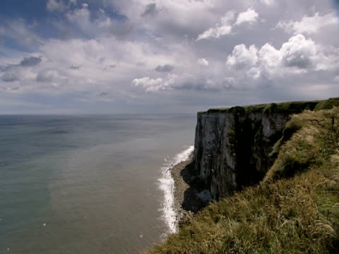 cliff face, waves lapping base, calm, blue sea and sky, tranquil, peaceful - ベンプトン点の映像素材/bロール