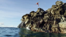 Cliff jumping back flip into blue ocean at sunset in slow motion