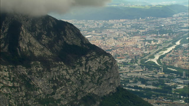 aerial ws cliff overlooking cityscape along isere river with alps in background / grenoble, france - grenoble stock-videos und b-roll-filmmaterial