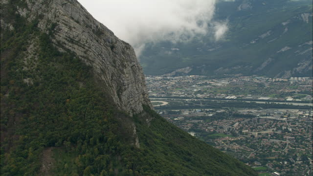 aerial ws cliff overlooking cityscape with european synchrotron radiation facility in background / grenoble, france - grenoble stock-videos und b-roll-filmmaterial