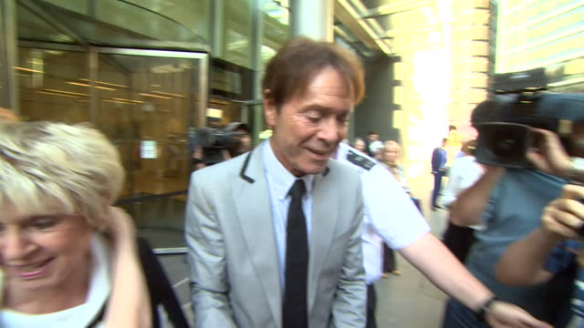 cliff richard and gloria hunniford leaving court where the singer is suing the bbc for invasion of privacy - グロリア ハニフォード点の映像素材/bロール