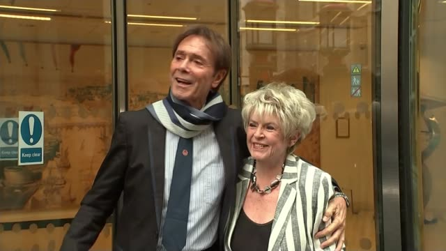 cliff richard criticises bbc over raid footage; england: london: high court: ext cliff richard and gloria hunniford along from court and waving to... - グロリア ハニフォード点の映像素材/bロール
